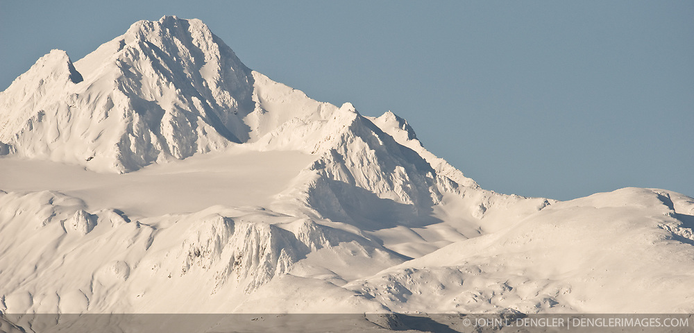 Four Winds Mountain near Haines, Alaska and near the border with Alaska and British Columbia, Canada are bathed in afternoon sunlight. The mountain can be seen from the Alaska Chilkat Bald Eagle Preserve.