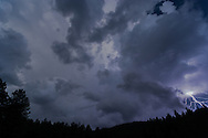 Lightning bolt and ominous storm clouds over mountain forest at twilight, © 2006 David A. Ponton
