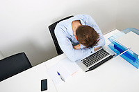 Tired businessman sleeping on laptop at desk in office