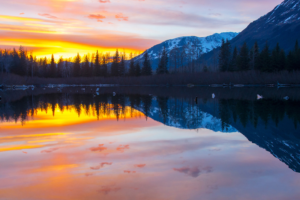 A mirror image reflection of a brilliant sunset on a flat calm pond with high mts. forming perfect duplication on the water.