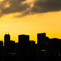 Chicago skyline panorama sunset photo. Panorama photo ratio is 1:3 and has a golden yellow backlit silhouette of downtown Chicago. Picture includes Willis Tower (Sears Tower) and many other downtown Chicago buidlings.