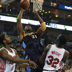 28 January 2009:  Denver Nuggets center Nene Hilario (31) shoots over Hornets defenders Hilton Armstrong (12) and Julian Wright (32) during a 94-81 win by the New Orleans Hornets over the Denver Nuggets at the New Orleans Arena in New Orleans, LA. The Hornets wore special throwback uniforms of the former ABA franchise the New Orleans Buccaneers for the game as they honored the Bucs franchise as a part of the NBA's Hardwood Classics series. .