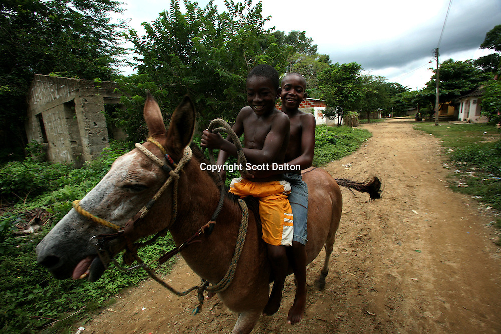 Two boys ride a donkey through the streets of San Basilio de Palenque, in northern Colombia, about 50 kilometers outside of Cartagena, on Tuesday, October 9, 2007. The town of San Basilio de Palenque, which was founded by runaway slaves at the beginning of the 17th century, is trying to maintain their native language known as Palenquero, a Spanish-based creole language whose unique grammar and African influences have astonished linguists. (Photo/Scott Dalton).
