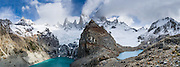 "On the border between Argentina and Chile, Mount Fitz Roy rises into clouds 2500 meters (8200 feet) above Lago Sucia (left) in Los Glaciares National Park, in the southern Andes mountains, Patagonia, Argentina, South America. Hike to the glacial cirque of Laguna de los Tres (right) from El Chaltén village, which was built in 1985 by Argentina to help secure the disputed border with Chile. The frontier tourist town of El Chaltén is 220 km (3 hours drive) north of the larger town of El Calafate. In 1877, explorer Perito Moreno named ""Cerro Fitz Roy"" for Robert FitzRoy (no space before the capital R) who, as captain of the HMS Beagle, had travelled up the Santa Cruz River in 1834 and charted much of the Patagonian coast. First climbed in 1952 by French alpinists Lionel Terray and Guido Magnone, Mount Fitz Roy (3405 meters or 11,170 feet elevation) has fickle, windy weather and is one of the world's most challenging technical ascents. It is also called Cerro Chaltén, Cerro Fitz Roy, and Monte Fitz Roy (with a space before the R). Chaltén comes from a Tehuelche (Aonikenk) word meaning ""smoking mountain"" (explained by frequent orographic clouds). Cerro is a Spanish word meaning hill. The foot of South America is known as Patagonia, a name derived from coastal giants, Patagão or Patagoni, who were reported by Magellan's 1520s voyage circumnavigating the world and were actually Tehuelche native people who averaged 25 cm (or 10 inches) taller than the Spaniards. Mount Fitz Roy is the basis for the Patagonia company's clothing logo, after Yvon Chouinard's ascent and subsequent film in 1968. Panorama stitched from 5 overlapping photos."