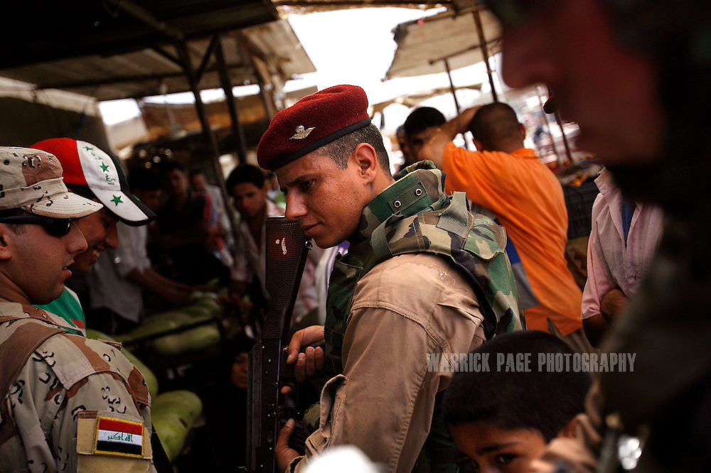 IRAQ, BASRA - JULY 5: An Iraqi soldier conducts a joint patrol through a crowded marketplace with US Marines in the poverty stricken neighborhood of Hayaniyah, July 5, 2008 in Basra, Iraq. When British forces withdrew in 2007, Basra deteriorated into street battles between numerous Shiite militias and criminal gangs. In April 2008, Iraqi prime minister, Nouri al Maliki, sent two Iraqi army divisions to retake control of Basra. While the fighting has ended, unemployment is rife, at about 70 per cent. Since early 2008, Iraq's security situation has improved with oil production increasing, record government surplus and easing sectarian tensions. (Photo by Warrick Page)