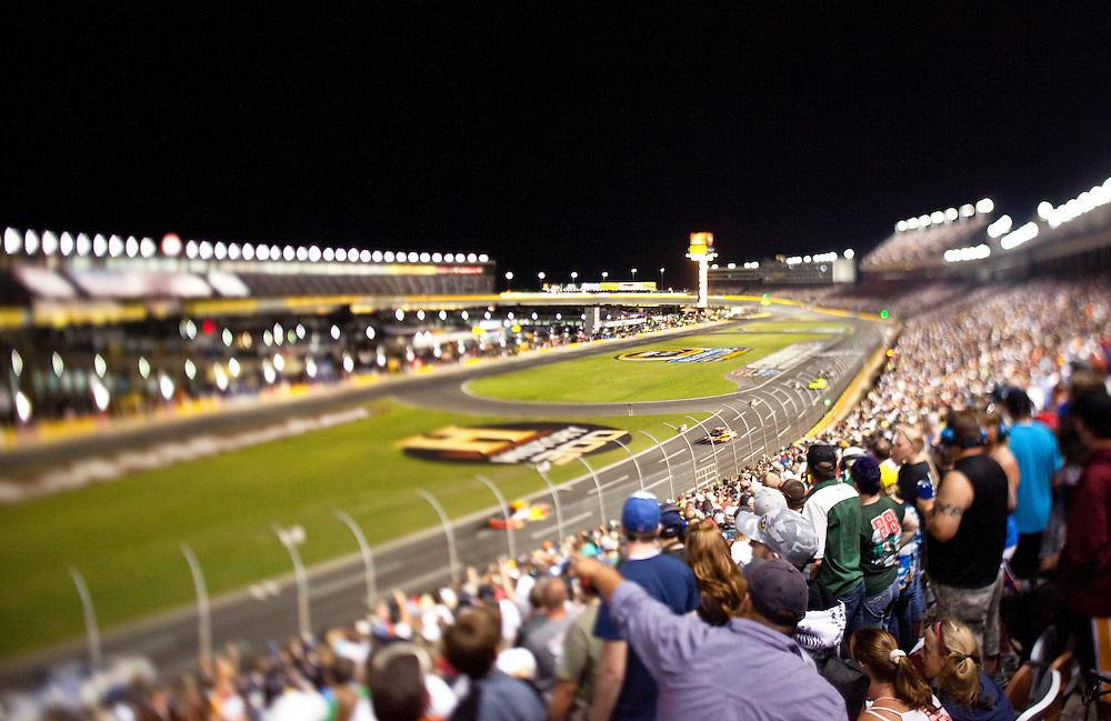 fans enjoying a night time race at Charlotte Motor Speedway