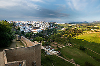 The old wall that surrounds the ancient city of Ronda, in southern Spain leads the eye to the white buildings of the Andalusian town.