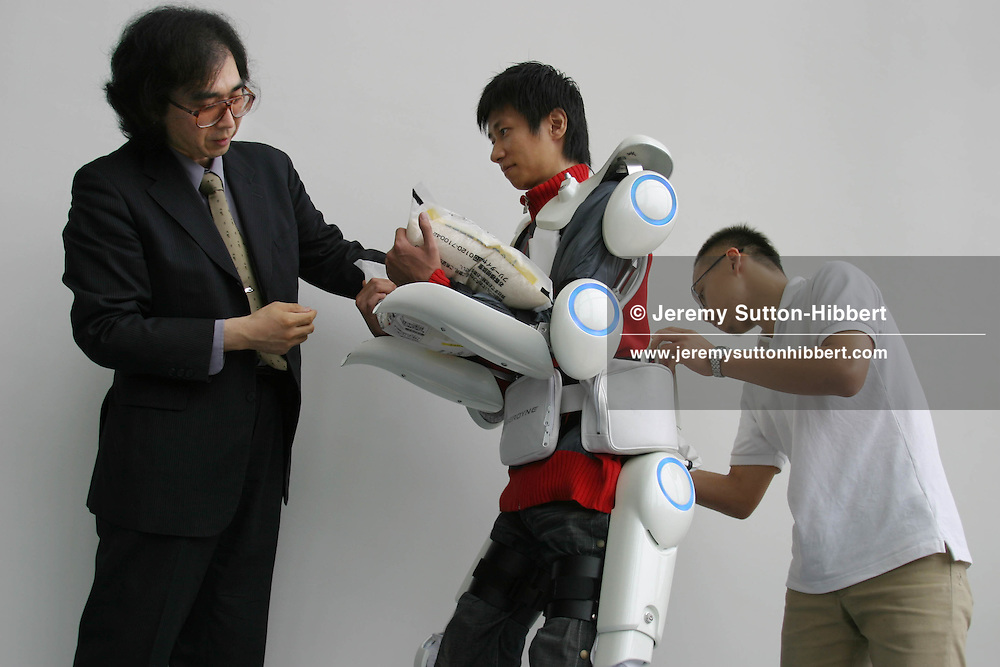 "Professor Yoshiyuki Sankai (on left), of the Cybernics Lab, University of Tsukuba, with a colleague (centre) wearing a prototype of the 'Cyberdyne HAL Robotsuit'. The wearer of the suit is enabled to lift heavy weights with ease, in University of Tsukuba, Tokyo, Japan, on Wednesday, June 29, 2005. The suit is an ""exo-skeleton type power assist system"" enabling the wearer to lift heavier weights than would be possible without the suit. ""Some sensors such as angle sensors, myoelectrical sensors, floor sensors etc. are adopted in order to obtain the condition of the HAL and the operator. All of the motordrivers, measurement system, computer, wireless LAN, and power supply are built in the backpack. Using the battery attached on the waist, HAL works as a complete wearable system""."