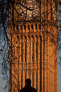 "The silhouetted statue of Sir Robert Peel and the clockface containing the Big Ben bell in the Elizabeth Tower of the British parliament, on 17th January 2017, in London England. The Elizabeth Tower (previously called the Clock Tower) named in tribute to Queen Elizabeth II in her Diamond Jubilee year – was raised as a part of Charles Barry's design for a new palace, after the old Palace of Westminster was largely destroyed by fire on the night of 16 October 1834. The new Parliament was built in a Neo-gothic style, completed in 1858 and is one of the most prominent symbols of both London and England. Sir Robert Peel, was a British statesman and member of the Conservative Party, served twice as Prime Minister of the United Kingdom and twice as Home Secretary. He created the modern police force and officers known as ""bobbies"" and ""peelers"""