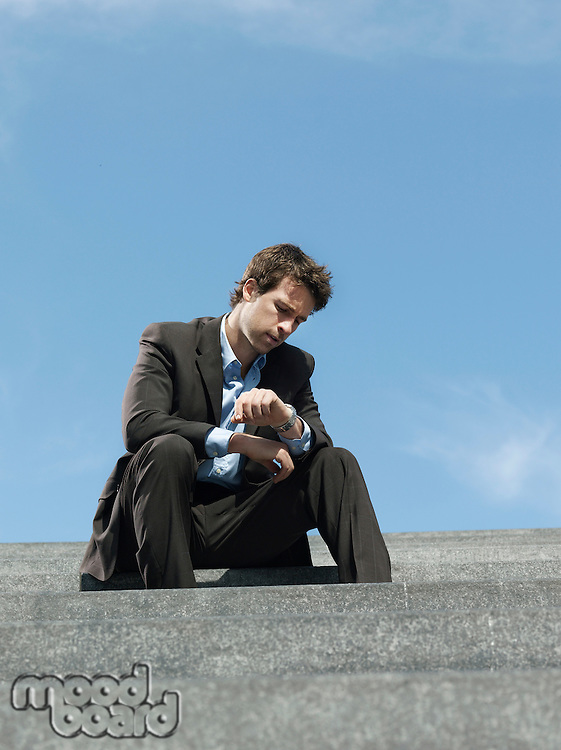 Businessman sitting on steps outdoors looking at wristwatch low angle view