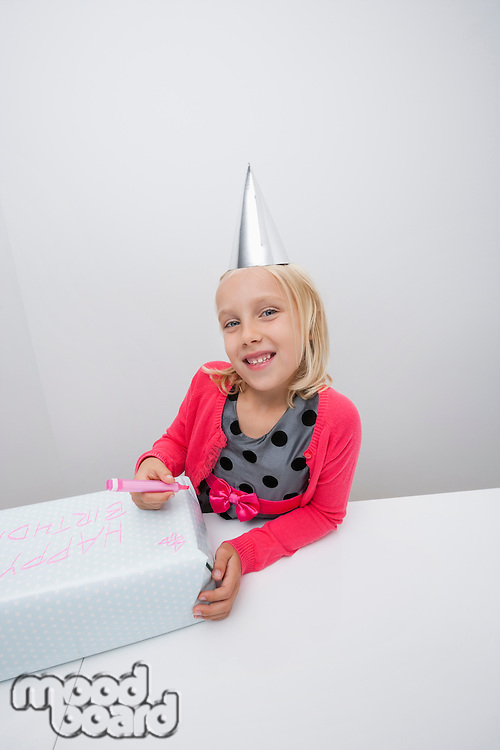 Portrait of girl preparing birthday gift at table in house