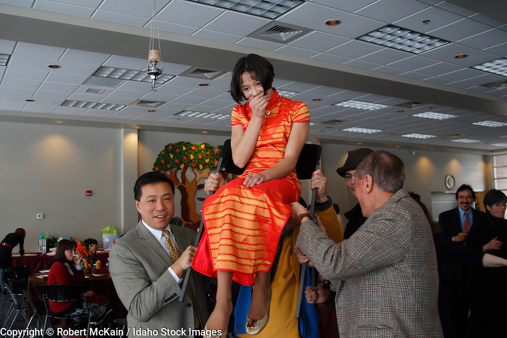 IDAHO. Boise. Asian Jewish girl lifted by her father and grandfather in chair for traditional Chair Dance at her Bat Mitzvah. December 2008. #pa080731 MR
