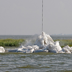 A helicopter drops 2,000 pound bags of sand into place, the bags dropped along the shoreline are used to prevent oil from reaching further into marshlands by creating a barrier off the coast west of Venice, Louisiana, U.S., on Tuesday, June 15, 2010.  Oil from Deepwater Horizon spill continues to impact areas across the coast of gulf states. (Mandatory Credit: Derick E. Hingle)