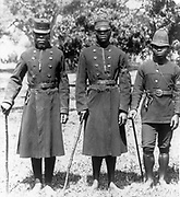 Black African Policemen  in uniform with police whistles, handcuffs handing from belts, and carrying sticks, Natal, South Africa between 1890 and 1920.
