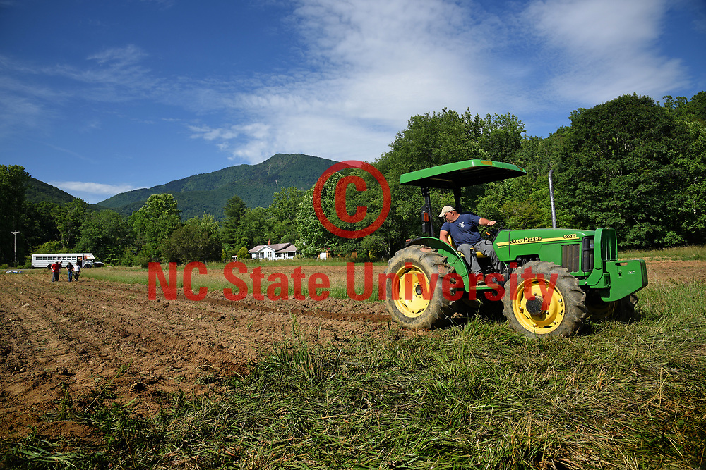 Yancey County cooperative extension agriculture technician Adam McCurry plows a field outside Micaville so FFA students can plant seeds.