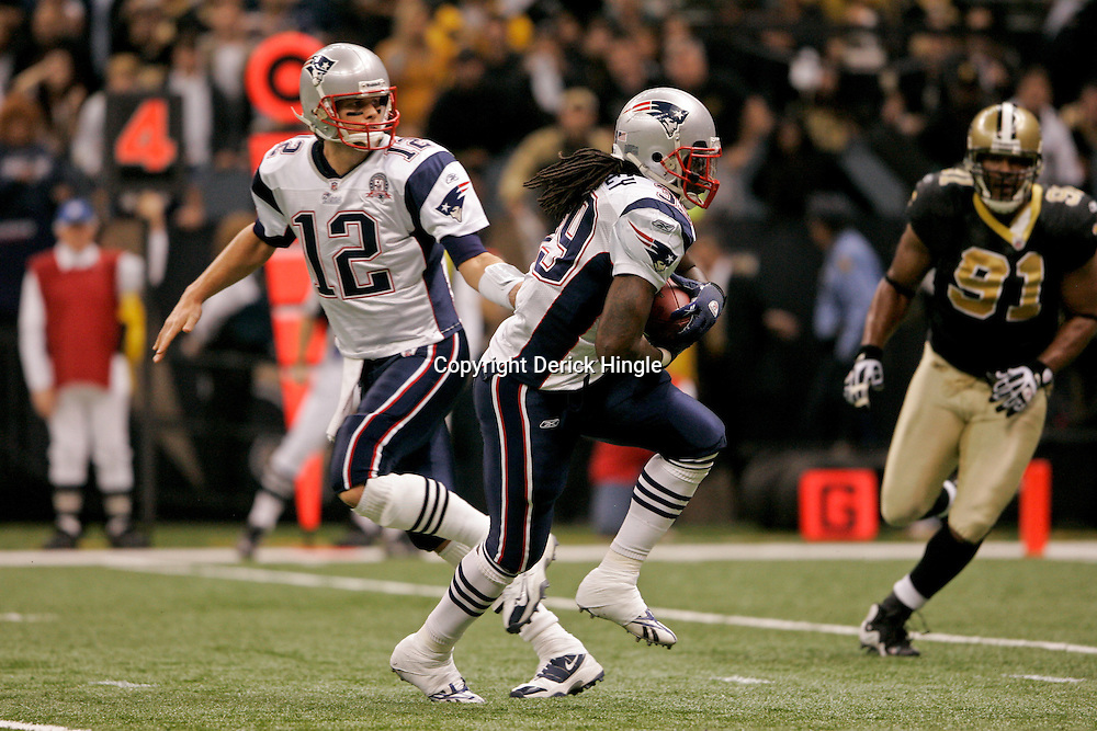 2009 November 30: New England Patriots quarterback Tom Brady (12) hands off to running back Laurence Maroney (39) during a 38-17 win by the New Orleans Saints over the New England Patriots at the Louisiana Superdome in New Orleans, Louisiana.