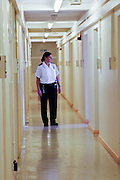 A female prison officer walking down a corridor of C wing at HMP Downview.