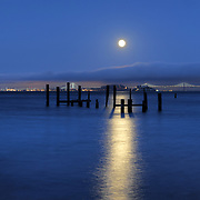 A supermoon rises over San Francisco Bay at dusk, as seen from the Sausalito waterfront.