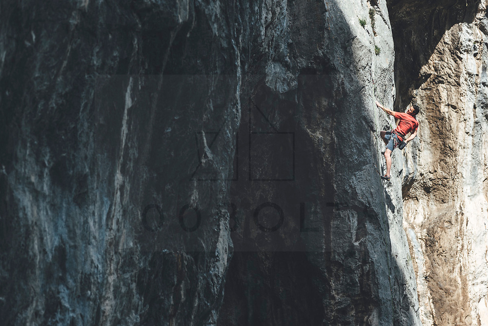Male climber climbing limestone wall wearing a red t-shirt Mamut climbing athlete Bobbi Bensman enjoying a climbing trip at Roca Verde, Asturias, Spain