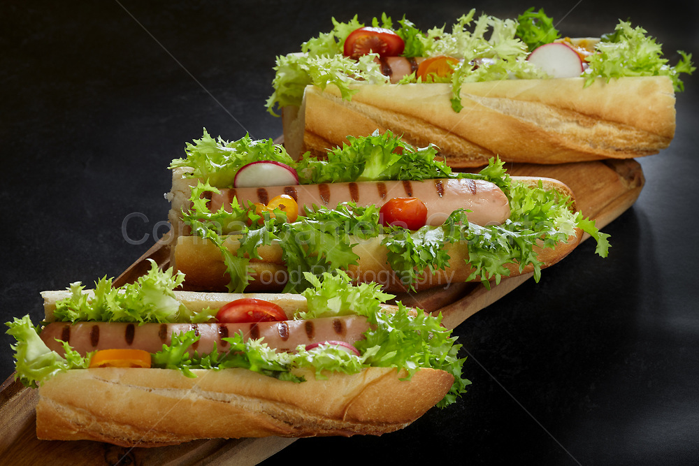Sub sandwiches with grilled wurst, salad, tomatoes and radish.