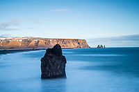 Arnardrangur Sea Stack viewed from the lower part of Dyrhólaey Peninsula: View over Reynisfjara black sand beach towards east. Reynisdrangar Sea stacks in background South Iceland.