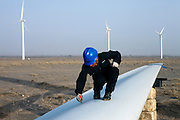 Gansu, China - 26 Feb 2010. A maintenance worker marks a blade of a windmill at Guazhou wind farm near Yumen, Gansu province, China. China has set a target for renewable energy consumption of 40 percent of the market by the year 2050.Photographer: Markel Rendondo/Greenpeace.