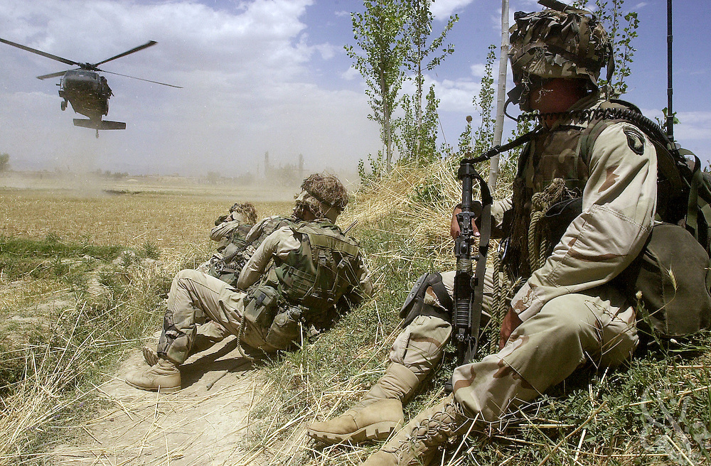 U.S. Army soldiers from the 101st Airborne watch from defensive positions as an inbound Blackhawk helecopter lands July 16, 2002 in village of Hesarak, eastern Afghanistan. The army raided the village to conduct a follow-up search for possible Al-Qaida or Taliban intelligence materials and to provide humanitarian aid. The raid was a follow-up to a similar raid there four days ago that yielded two detainees and undisclosed intelligence materials.