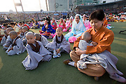 The annual Lotus Lantern Festival is held to celebrate Buddha's Birthday. Opening ceremony for the parade at Dongdaemun Stadium. Little monk fallen asleep in supervisor's lap.