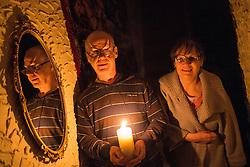 © Licensed to London News Pictures . 24/03/2013 . L-R Ken Jones (65) and Ann Jones (70) of 65 New Barton Street , Salford , wrap up warm and use a candle to light their way around their house . A power cut in Salford this evening (24th March) has left dozens of homes without power in freezing temperatures . Photo credit : Joel Goodman/LNP