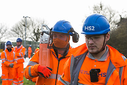 Harefield, UK. 8 February, 2020. HS2 engineers carry a chainsaw in order to carry out tree felling works for the high-speed rail project. The activists were successful in preventing any of the scheduled tree felling by HS2 and after an intervention by a police officer all tree felling and strimming work has now been cancelled for the weekend.