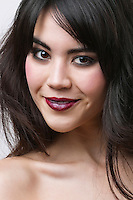 Close-up portrait of mixed race young woman over white background