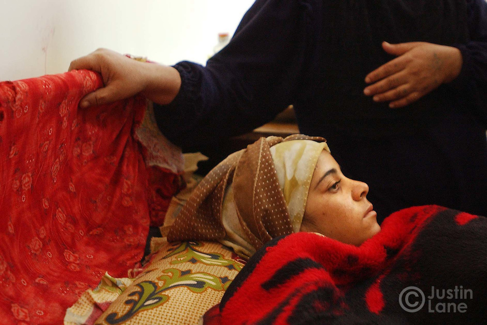 09/21/03--Faluja, Iraq--16-year-old Manal Turky is seen lying in a hospital bed with her mother looking over her after being shot by American soldiers. Turky was injured when a convoy of American soldiers opened fire on the family's home on Sept. 12, 2003, for yet-to-be-determined reasons, killing  a 2-year-old girl and injuring 4 others.