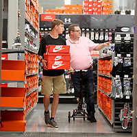 Bryce McKee, of Ripley, looks at shoes with his dad Stacy, during the tax free weekend while shopping at Academy Sports in Tupelo on Friday.