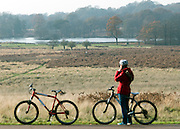 © Licensed to London News Pictures. 29/11/2014. Richmond, UK. Cyclists stop to take in the view.  People and animals enjoy the late Autumn sunshine in Richmond Park, Surrey, today 29th November 2014. Photo credit : Stephen Simpson/LNP