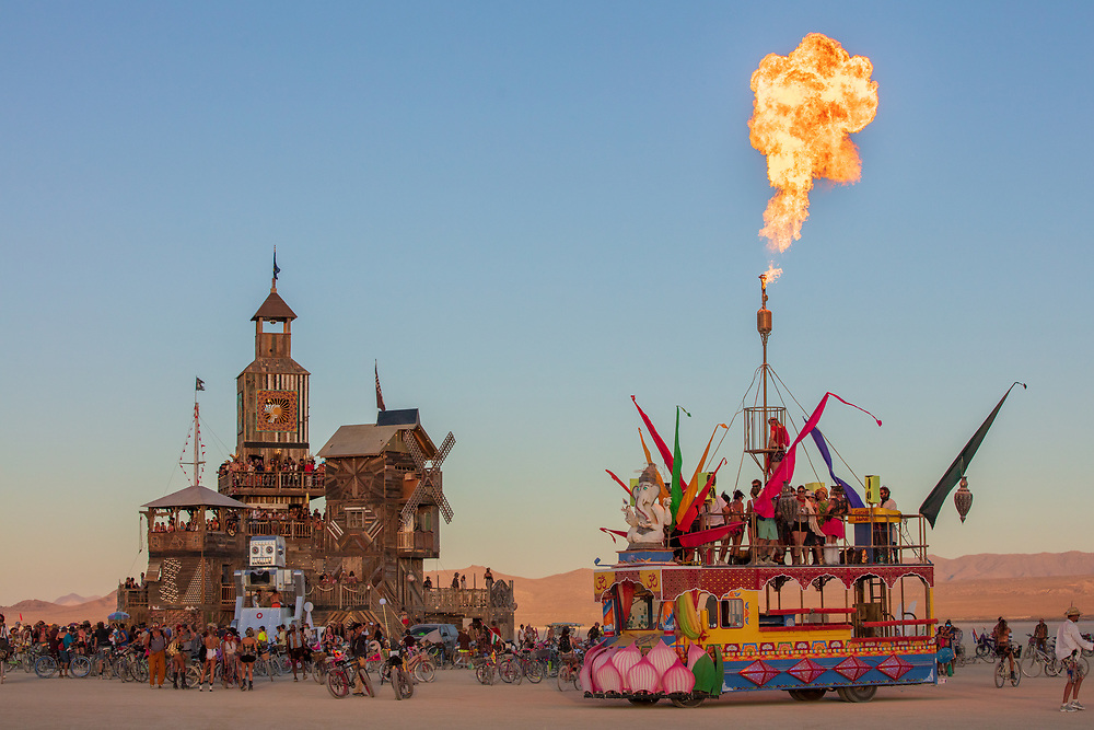 The Folly and Unknown Mutant Vehicle with Flame<br /> by: Dave Keane & The Folly Builders<br /> from: San Francisco, CA<br /> year: 2019<br /> <br /> The Folly represents an imaginary shantytown of funky climbable towers and old western storefronts, cobbled together from salvaged and reclaimed lumber from original San Francisco Victorians to be reborn in the desert, affording shelter, entertainment and perspective to the community.<br /> <br /> URL: www.thefollybrc.com<br /> Contact: info@thefollybrc.com<br /> <br /> https://burningman.org/event/brc/2019-art-installations/?yyyy=&artType=H#a2I0V000001AVkAUAW