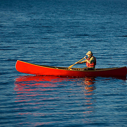 A man paddles his canoe on Seboeis Lake near Millinocket, Maine.