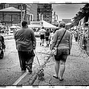 This black and white street scene from Bastille Days in Milwaukee show s a little dog walking with his owners. Photo by Jennifer Rondinelli Reilly. All Rights Reserved. NO USE WITHOUT PERMISSION.