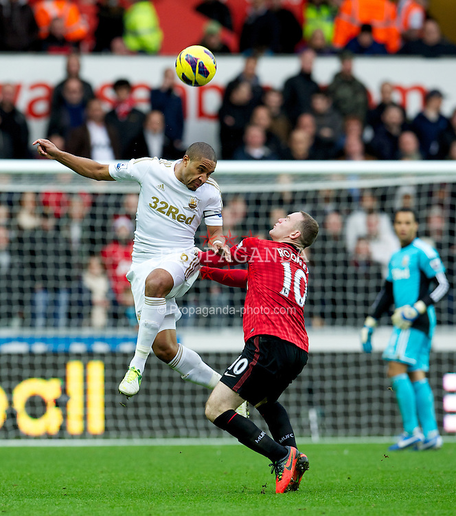 SWANSEA, WALES - Sunday, December 23, 2012: Manchester United's Wayne Rooney in action against Swansea City's captain Ashley Williams during the Premiership match at the Liberty Stadium. (Pic by David Rawcliffe/Propaganda)