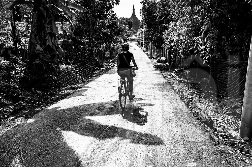 Tourist cycles on a countryside deserted road, Mrauk U, Rakhine State, Myanmar, Asia