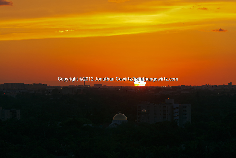 The setting sun bathes Miami International Airport and the western Miami, Florida skyline in warm, orange light. WATERMARKS WILL NOT APPEAR ON PRINTS OR LICENSED IMAGES.