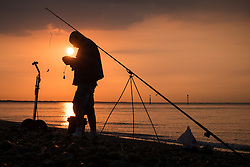 © Licensed to London News Pictures. 15/09/2016. Portsmouth, UK.  A man fishing next to Southsea Parade Pier as the sun rises this morning, 15th September 2016. Photo credit: Rob Arnold/LNP