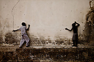 Boys play on a pockmarked wall after their town was attacked by mutinous SPLA troops.