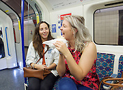 Sadia Khan at London's Night Tube launch at Brixton tube station, London, Great Britain <br /> 19th August 2016 <br /> <br /> girls eating a kebab on tube <br /> <br /> Sadia Khan, mayor of London,  launched the first night tube service and travelled on a tube train between Brixton and Walthamstow on the Victoria Line. <br />  <br /> He launched the first 24 hour Friday and Saturday night services on the Central and Victoria lines <br /> <br /> Photograph by Elliott Franks <br /> Image licensed to Elliott Franks Photography Services