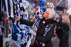 © Licensed to London News Pictures. 30/01/2018. The funeral of footballer Cyrille Regis took place in West Bromwich today. The hearse made it's way past the football ground where he played as family, friends and fans said their final farewell. Pictured, people pictured outside the Hawthorns in front of the tributes paid. Photo credit: Dave Warren/LNP