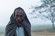 Farmer with Longyi on his head to keep warm, Pathein