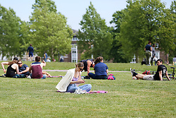 © Licensed to London News Pictures. 17/05/2020. London, UK. Members of the public relax in Finsbury Park, north London on the first weekend since the government relaxed the rules on the COVID-19 lockdown, allowing people to spend more time outdoors whilst following social distancing guidelines. According to the Met Office, warmer weather is forecast in the coming week and over the bank holiday weekend. Photo credit: Dinendra Haria/LNP