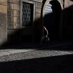 Bergamo, Italy - A woman walks in the historical centre of Upper Bergamo (Bergamo Alta) at sunset