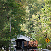 Located off the McKenzie River highway near Vida, the Goodpasture Bridge is one of the most popular covered bridges in Oregon. A log truck heading under the bridge.
