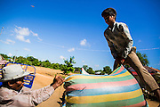 "29 JUNE 2013 - BATTAMBANG, CAMBODIA:   Workers at a rice mill load bags of milled rice onto a tractor. The mill is next to the tracks that carry the ""bamboo trains."" The bamboo train, called a norry (nori) in Khmer is a 3m-long wood frame, covered lengthwise with slats made of ultra-light bamboo, that rests on two barbell-like bogies, the aft one connected by fan belts to a 6HP gasoline engine. The train runs on tracks originally laid by the French when Cambodia was a French colony. Years of war and neglect have made the tracks unsafe for regular trains.  Cambodians put 10 or 15 people on each one or up to three tonnes of rice and supplies. They cruise at about 15km/h. The Bamboo Train is very popular with tourists and now most of the trains around Battambang will only take tourists, who will pay a lot more than Cambodians can, to ride the train.       PHOTO BY JACK KURTZ"