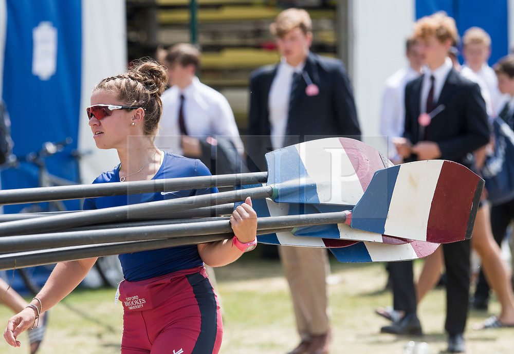 © Licensed to London News Pictures. 04/07/2018. Henley-on-Thames, UK. A rower form Oxford Brookes Rowing Club carrying her oars at day one of the Henley Royal Regatta, set on the River Thames by the town of Henley-on-Thames in England. Established in 1839, the five day international rowing event, raced over a course of 2,112 meters (1 mile 550 yards), is considered an important part of the English social season. Photo credit: Ben Cawthra/LNP